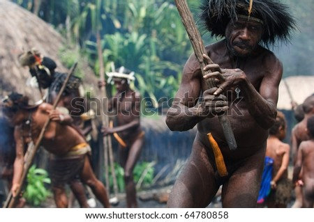 CENTRAL PAPUA, NEW GUINEA - JUNE 25: The Papuan banishes from the village, swinging a stick. Indonesia. Village of people Dani Dugum. On June, 2009 in Papua New Guinea. - stock photo