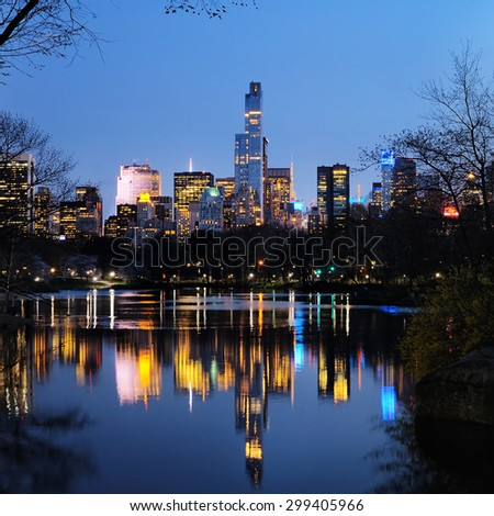 Central Park in dusk and buildings reflection in midtown Manhattan New York City - stock photo