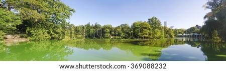 Central Park, New York City, Usa: pond, reflections and the Loeb Boathouse Central Park on September 14, 2014. The Loeb Boathouse Central Park is an iconic restaurant popular since 1860 - stock photo