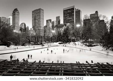 Central Park Winter Scene and Skyscrapers in Black & White. Ice skating on the Wollman Rink in wintertime, Central Park, Manhattan, New York City. - stock photo