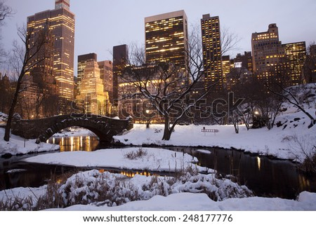 Central park with Manhattan buildings at the background in New York City.  Snow day at winter. - stock photo