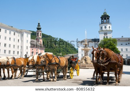 Central place in Salzburg city , Austria with carriages and horses - stock photo