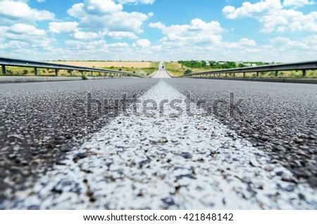central white line on asphalt road closeup and blue sky. soft focus - stock photo