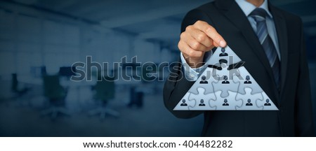 CEO, leadership and corporate hierarchy concept - recruiter complete team represented by puzzle in pyramid scheme by one leader person (CEO). Wide banner composition with office in background.
