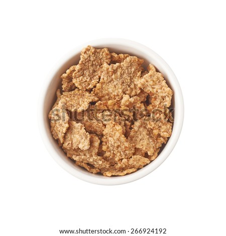 Ceramic bowl filled with the brown whole grain cereal flakes, composition isolated over the white background, top view above foreshortening - stock photo