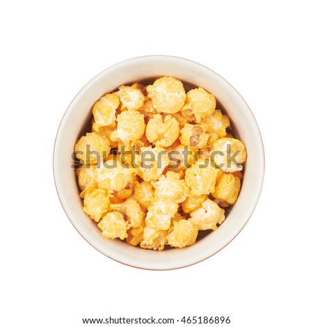 Ceramic bowl full of cheese flavoured orange popcorn flakes isolated over the white background, top view above