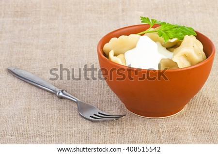 Ceramic bowl with meat dumplings, and fork near - stock photo