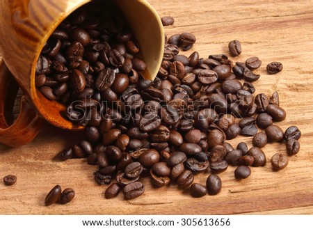 Ceramic coffee mug with coffee beans on wood.