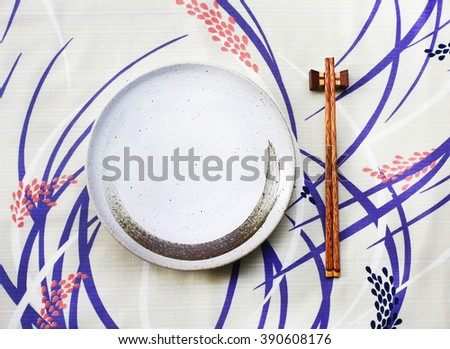 ceramic dish (plate) and chopsticks on table.Flat lay - stock photo