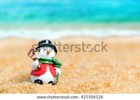 Ceramic figurine of a snowman wearing a hat and scarf  in the sand on the background of beach and sea - stock photo