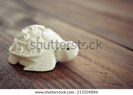 Ceramic figurine of turtle on wooden background - stock photo