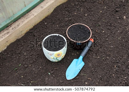 Ceramic flowerpots filled with the fresh soil for planting and a garden trowel in the polycarbonate greenhouse prepared for wintering