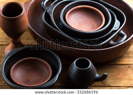 Ceramic handmade pottery earthenware utensil, kitchenware on the wooden table background - stock photo