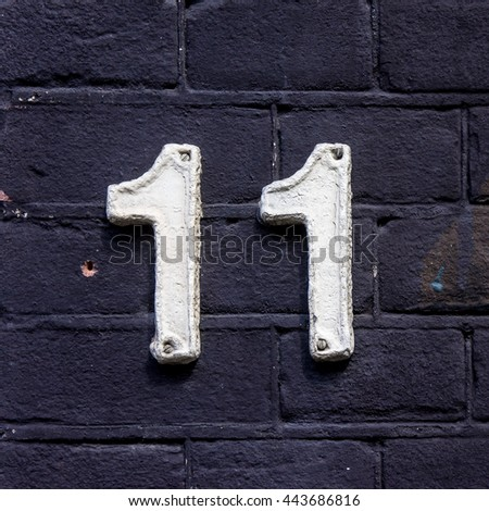 ceramic house number eleven, painted white - stock photo