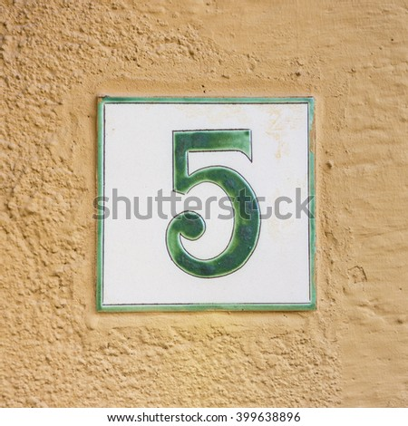 Ceramic house number five on a plastered wall - stock photo