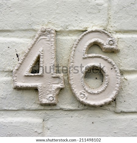 Ceramic house number forty six. White lettering on a white wall - stock photo