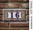 ceramic house number sixteen, surrounded by a decoration of flowers - stock photo