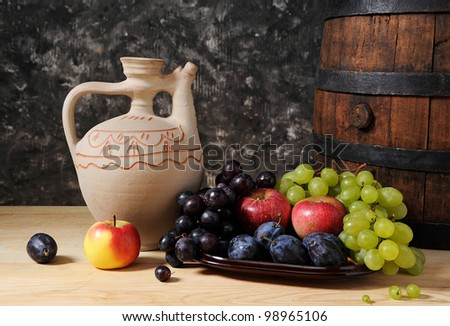 Ceramic jug, barrel and fruit on the table - stock photo