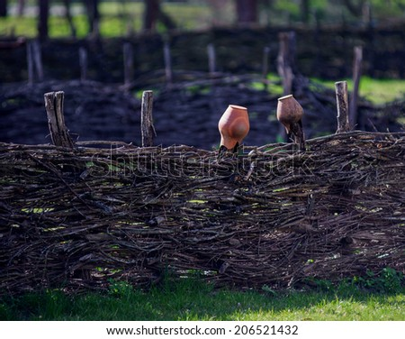 ceramic jug hanged on a wooden fence. Old traditional clay jug hanging on the wooden fence  - stock photo