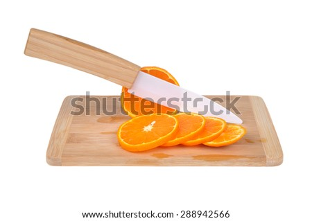 Ceramic knife, chopping board and orange, tangerine isolated