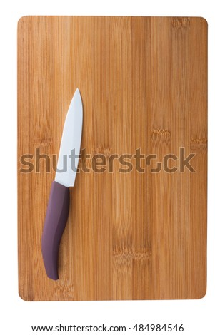 ceramic knife with a purple pen on a bamboo cutting board.