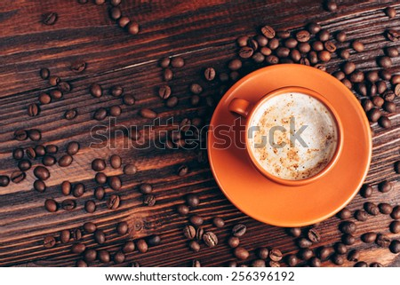 Ceramic orange cup of coffee with foam and coffee beans, lying on wooden table - stock photo