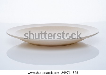 Ceramic plate on the white table top - stock photo