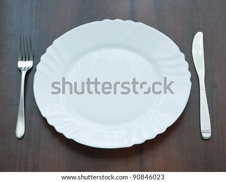 Ceramic plate with knife and fork on wooden background - stock photo