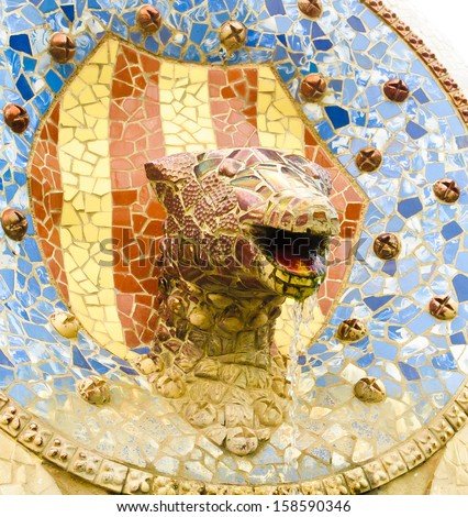 Ceramic snake head fountain in Parc Guell designed by Antoni Gaudi, Barcelona, Spain.  - stock photo