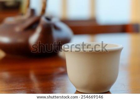 ceramic tea pot and cup on wood table - stock photo