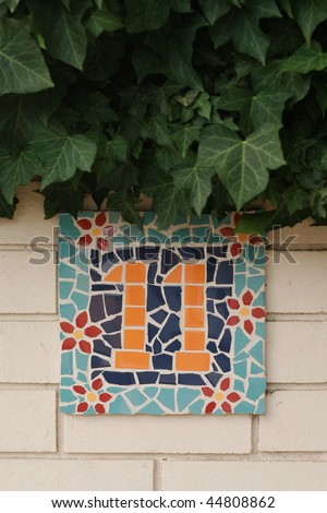 ceramic tile number eleven against brick wall - stock photo