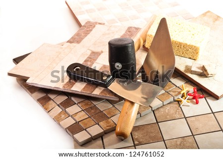 Ceramic tile, trowel, a rubber hammer and trowel on a white background - stock photo