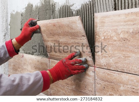 Ceramic Tiles. Tiler placing ceramic wall tile in position over adhesive - stock photo