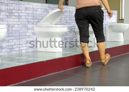 Ceramic toilet and lady's feet, closeup of photo - stock photo
