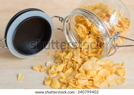 cereal cornflakes spilling out from the glass jar - stock photo