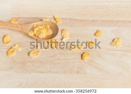 cereal cornflakes spilling out from the wood spoon to wood floor - stock photo