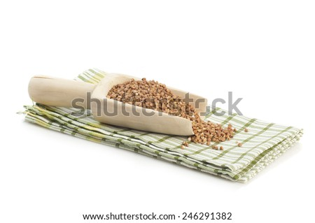 Cereal seria: Buckwheat groats in wooden scoop on checkered napkin isolated on white background - stock photo
