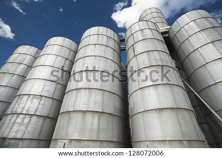 Cereal silos under the blue sky.A row of grain silos set in an agricultural processing plant - stock photo