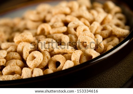 Cereal - This is a shot of a bowl full of cereal shot on a brown background with a shallow depth of field. - stock photo