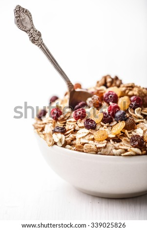 Cereal with dried cranberries, black and golden raisins,fruits and maple syrup. Healthy eating