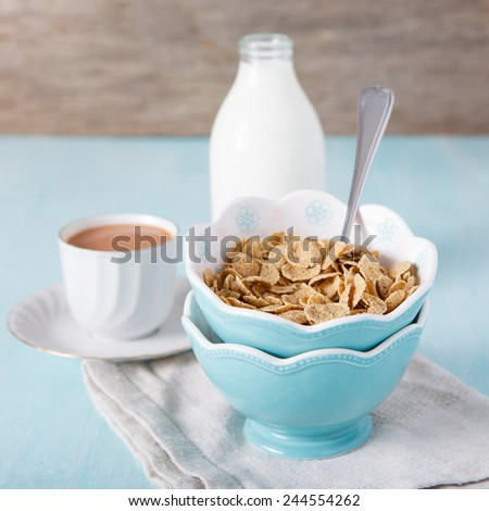 Cereals in the blue bowl with milk and coffee on the background, selective focus - stock photo