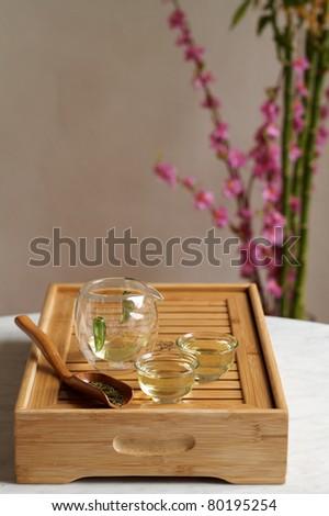 Ceremonial glass tea set on wooden board - stock photo