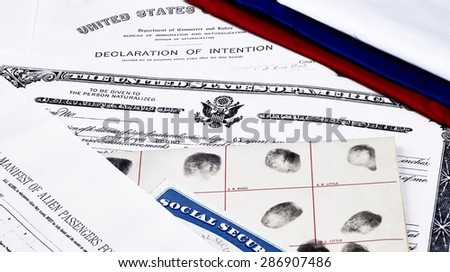 Certificate of US Citizenship, social security card, declaration of intention, and passenger manifest with red, white and blue ribbon - stock photo