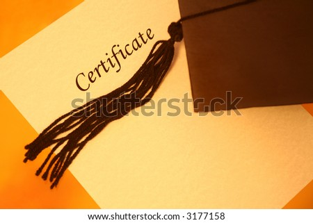 certificate printed on a yellowish grainy textured paper and a black graduation cap on yellow-orange background, top view - stock photo