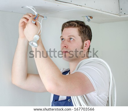 Certified electrician installing socket for light bulb - stock photo