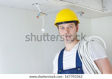Certified electrician worker in yellow hardhat - stock photo