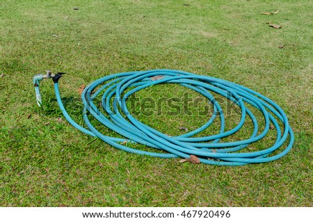 Cerulean rubber tube on green grass in garden