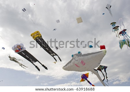 CERVIA, ITALY - MAY 1: Sky full of kites for International Kite Festival on May 1, 2010 in Cervia, Italy. This Festival brings together kite flyers from all over the world every year since 1981. - stock photo