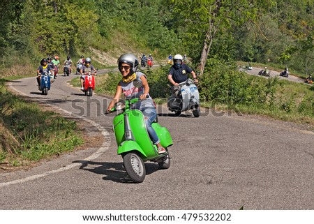 "CESENA, ITALY - JUNE 26: biker girl leads a group of bikers riding a vintage italian scooter Vespa on the hills during the rally ""I colli di Romagna"" on June 26, 2016 in Cesena, FC, Italy"