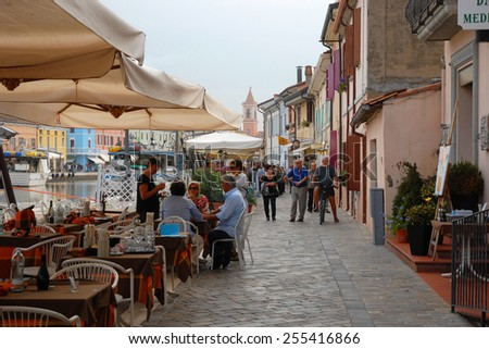 CESENATICO, ITALY- SEPTEMBER 21, 2014: locals and tourist relaxing at the harbor. The harbor designed by Leonardo da Vinci attracts thousands of tourists every month - stock photo